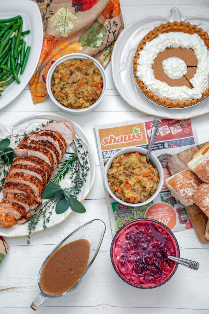 overhead view of full Thanksgiving dinner, including turkey breast, stuffing, cranberry sauce, rolls, pumpkin pie, and gravy