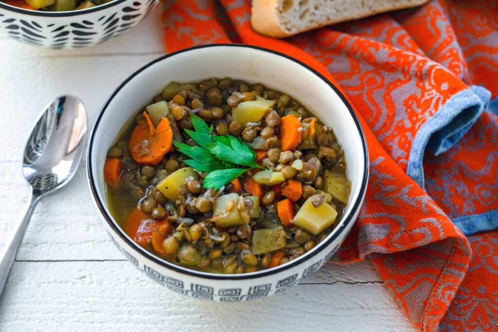 Landscape view of bowl of lentil soup topped with parsley with spoon next to bowl