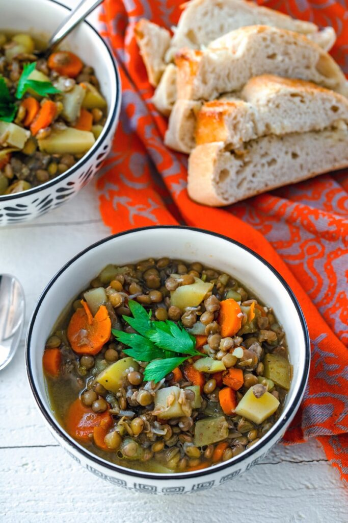 overhead view of bowl of soup with lentils, potatoes, carrots, and broth with second bowl of soup, spoon, and sliced bread in background