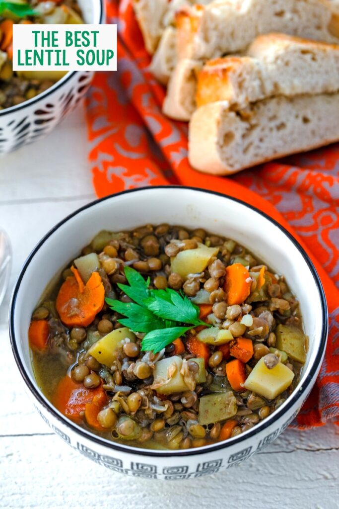 The best lentil soup in a bowl packed with lentils, carrots, potatoes, and broth with parsley on top with bread in the background and recipe title at top of photo