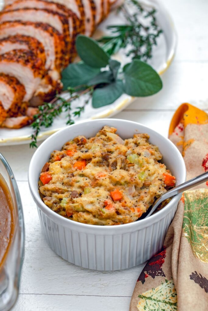 Head-on view of Thanksgiving stuffing in small casserole dish with turkey platter in background