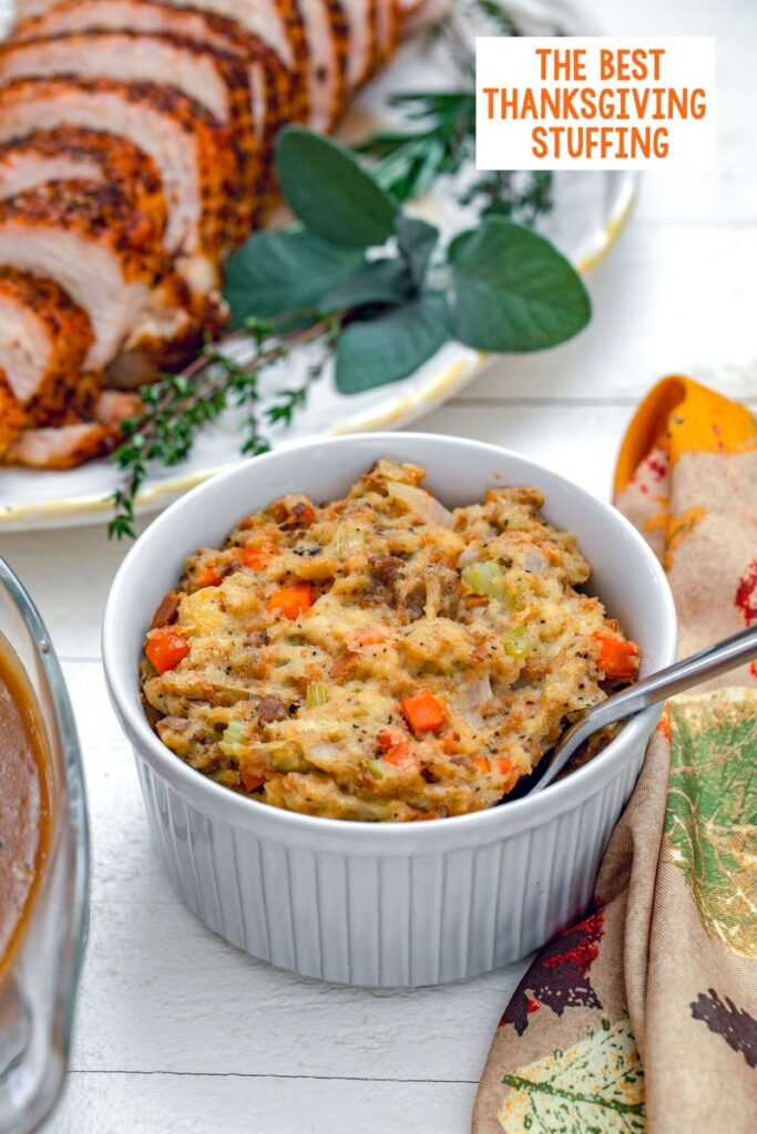 Head-on view of Thanksgiving stuffing in small casserole dish with turkey platter in background and recipe title at top