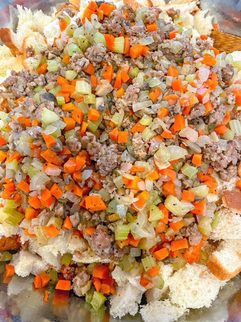 Vegetables and sausage over white bread in bowl