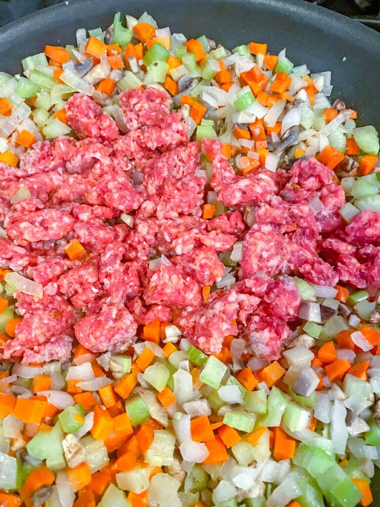 Vegetables cooking in a skillet with sausage