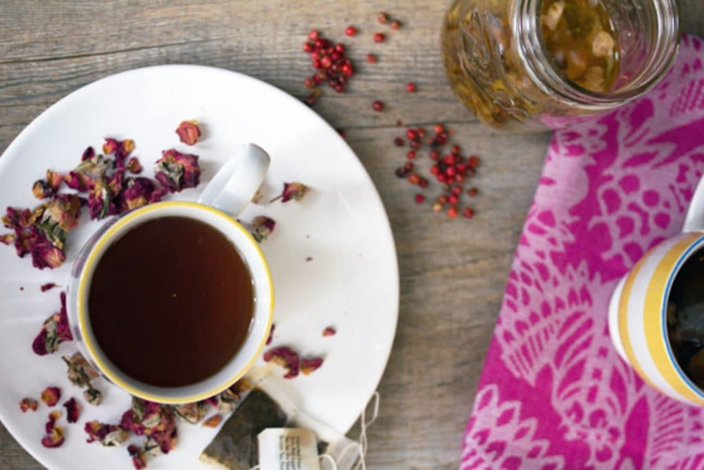 Overhead view of English rose cocktail in a teacup on a white plate surrounded by dried rosebuds with pink peppercorns, a teabag, and jar of simple syrup