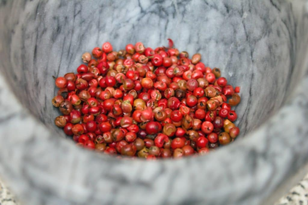 View of pink peppercorns ready to be crushed with a mortar and pestle