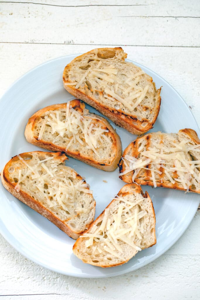 Toasted bread slices with parmesan cheese grated on top