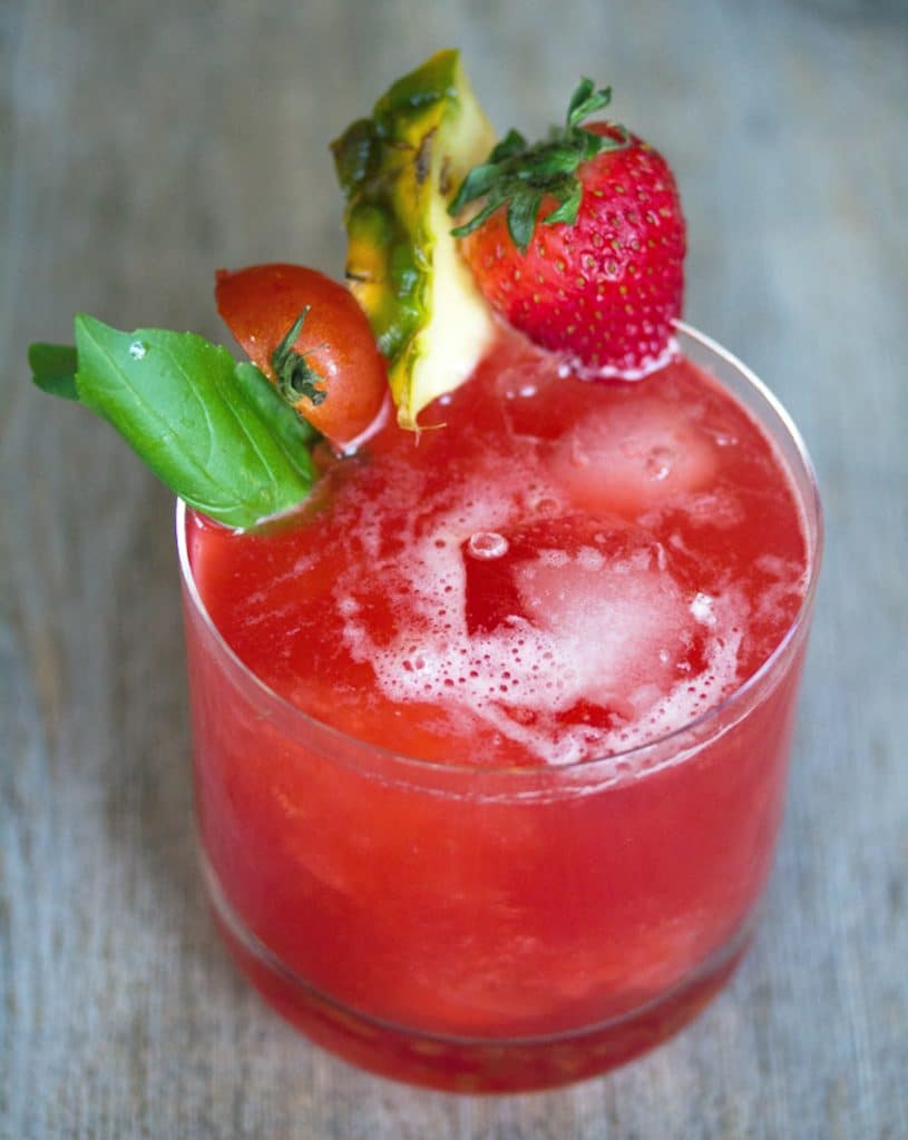 View of bright red tomato Campari cocktail with strawberry, pineapple, tomato, and basil garnish