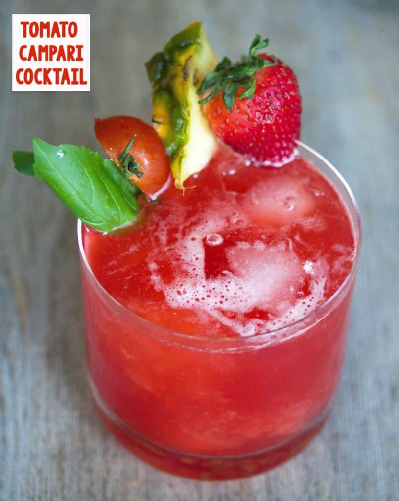 View of bright red tomato Campari cocktail with strawberry, pineapple, tomato, and basil garnish and recipe title at top