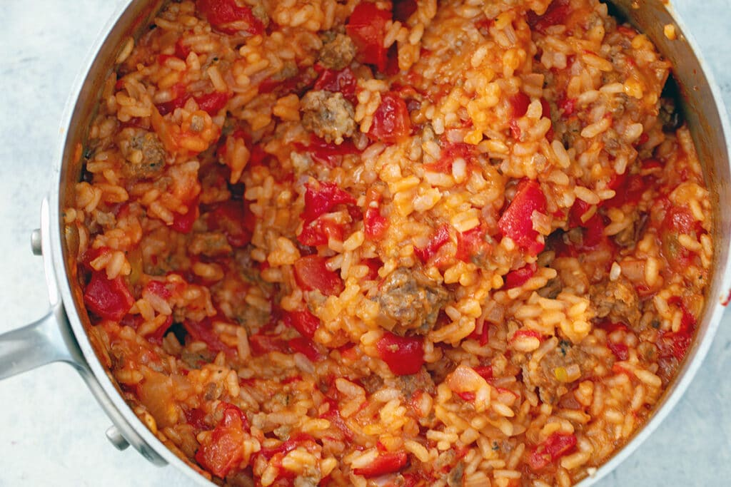 Risotto with tomatoes and sausage cooking in saucepan
