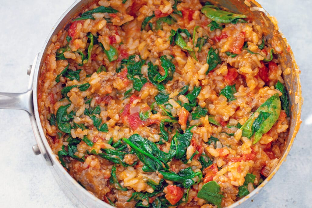 Risotto with tomatoes, sausage, and spinach mixed in