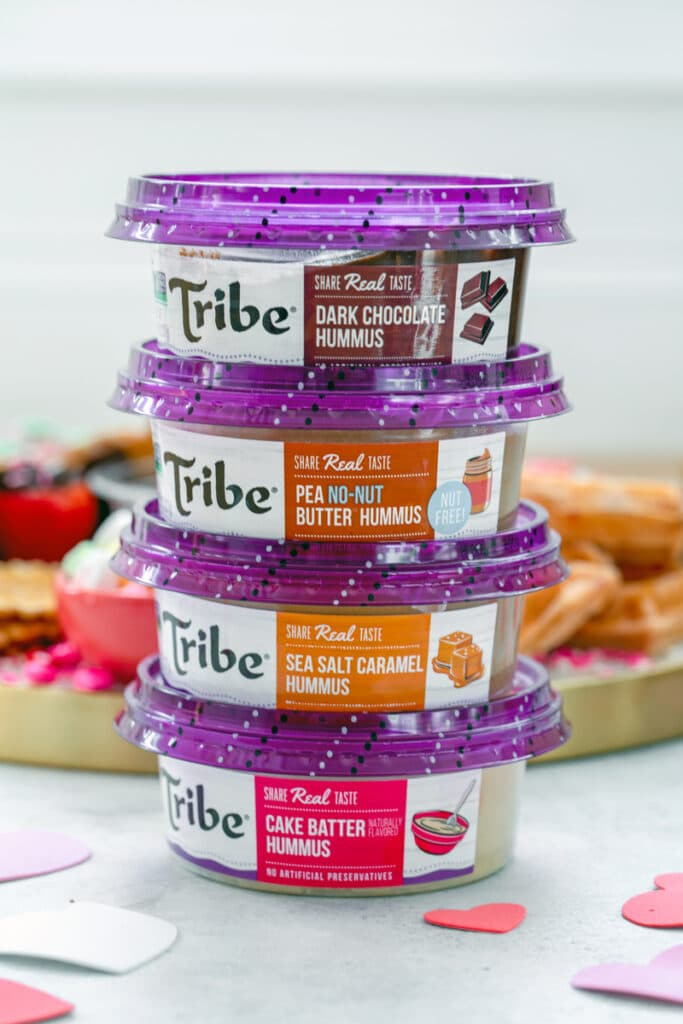 Head-on view of a stack of multiple Tribe dessert hummus containers, including dark chocolate, pea no-nut putter, sea salt caramel, and cake batter