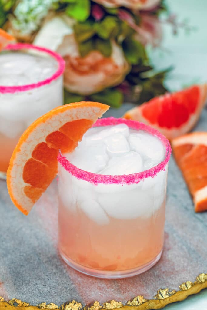 Close-up view of a triple grapefruit fizz cocktail with grapefruit wedge garnish and grapefruit wedges and flowers in the background