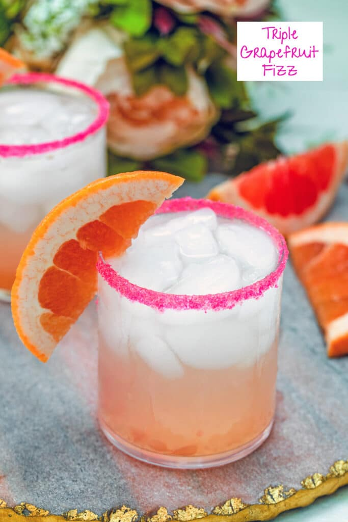 Close-up view of a triple grapefruit fizz cocktail with grapefruit wedge garnish and grapefruit wedges and flowers in the background with recipe title at top