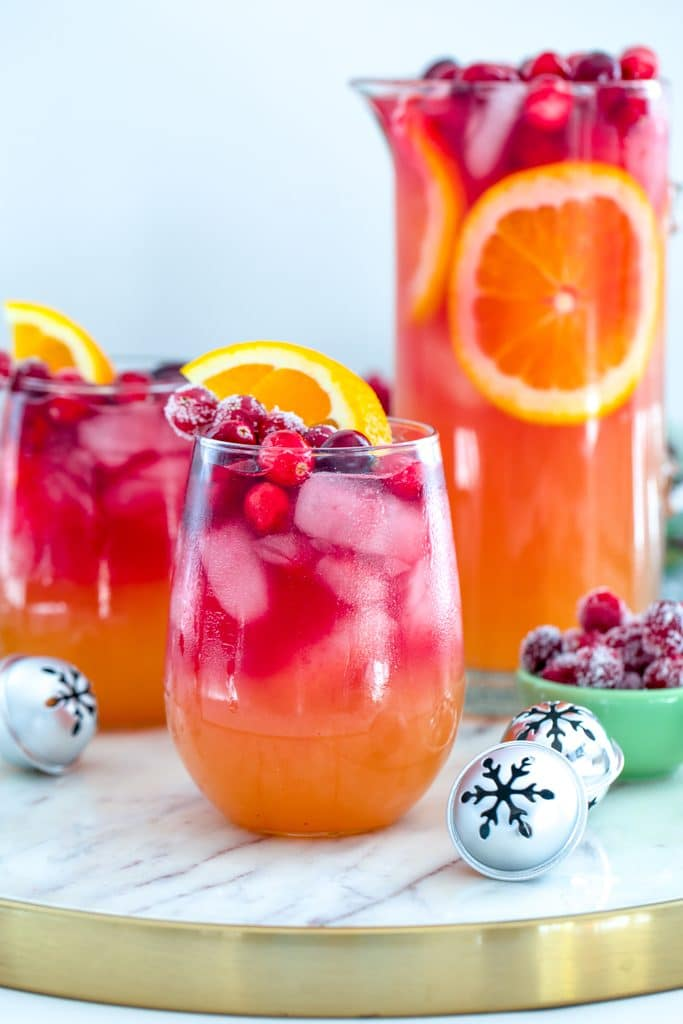 Head-on view of glass of tropical cranberry sangria with second glass, pitcher, mini holiday bells, and bowl of sugared cranberries in the background