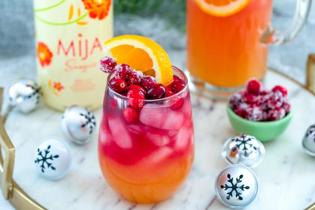 Landscape overhead view of glass of tropical cranberry sangria on a gold and marble surface surrounded by bottle of white Mija Sangria, mini holiday bells, and sugared cranberries