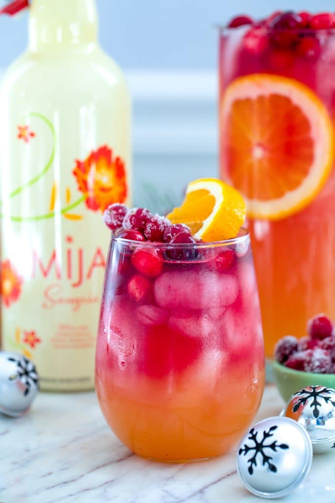 Head-on closeup view of glass of tropical cranberry sangria with bottle of white Mija sangria, pitcher of sangria and mini holiday bells in the background