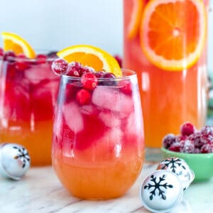 Tropical Cranberry Sangria -- Your favorite summer drink just transitioned to winter! This Tropical Cranberry Sangria is made with Mija Sangria, orange juice, and fresh cranberry juice. It will have you serving winter sangria all holiday season long | wearenotmartha.com #sangria #cranberries #holidays #christmas