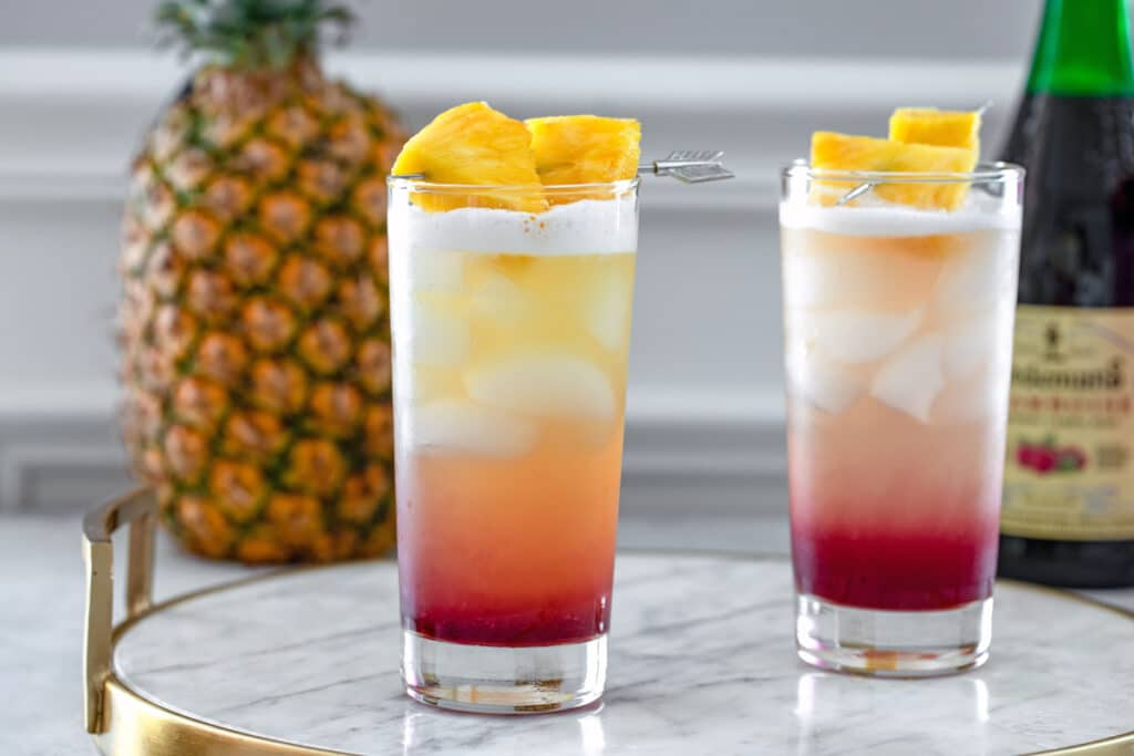 Landscape head-on view of two tropical gin sunrise cocktails on a marble tray with whole pineapple and bottle of raspberry lambic in background