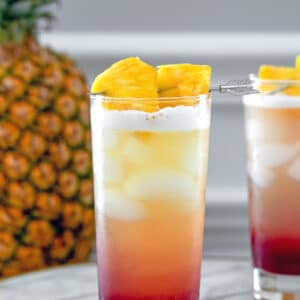 Tropical Gin Sunrise -- Tropical Gin Sunrise cocktails are a visually stunning combination of pineapple juice, gin, raspberry lambic and lemon juice. They're easy to mix and perfect for summer sipping! | wearenotmartha.com #gin #cocktails #tropicaldrinks #gindrinks