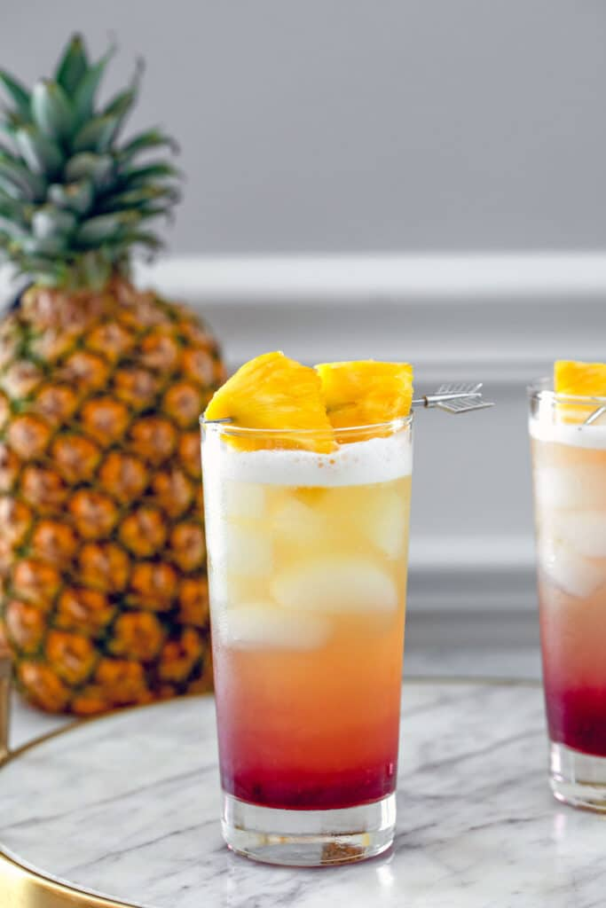Head-on view of tropical gin sunrise cocktail on a marble tray with pineapple garnish and whole pineapple in the background
