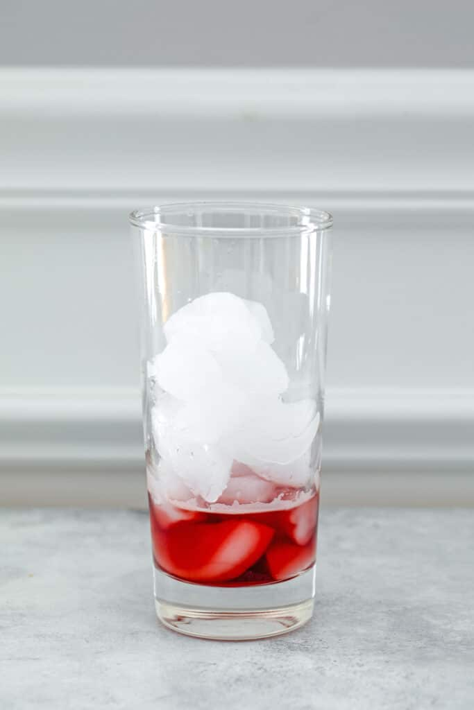 Head-on view of glass filled with ice with raspberry lambic on bottom
