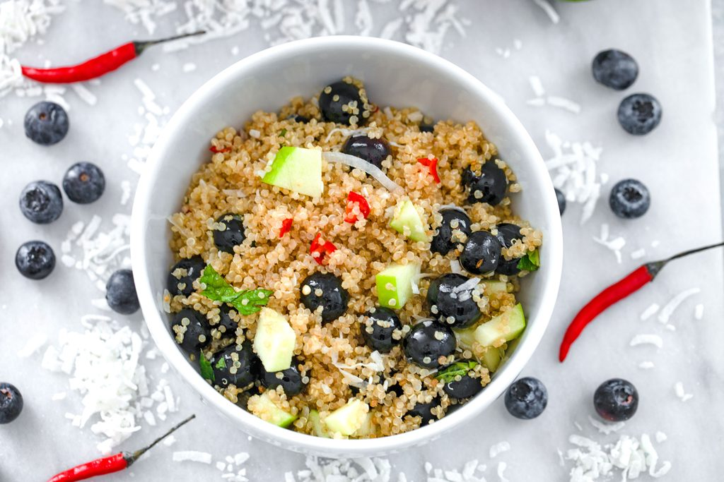 Landscape overhead view of a white bowl of tropical quinoa salad on a marble surface with shredded coconut, blueberries, and red chili peppers all around