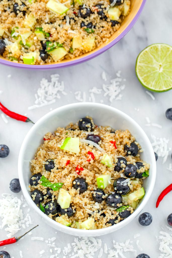 Bird's eye view of a white bowl of tropical quinoa salad on a marble surface with shredded coconut, blueberries, red chili peppers, a lime half, and large serving bowl of salad in background