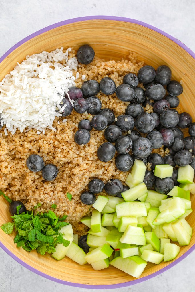 Overhead view of a serving bowl filled with quinoa, blueberries, shredded coconut, chopped green apples, and chopped mint before being tossed
