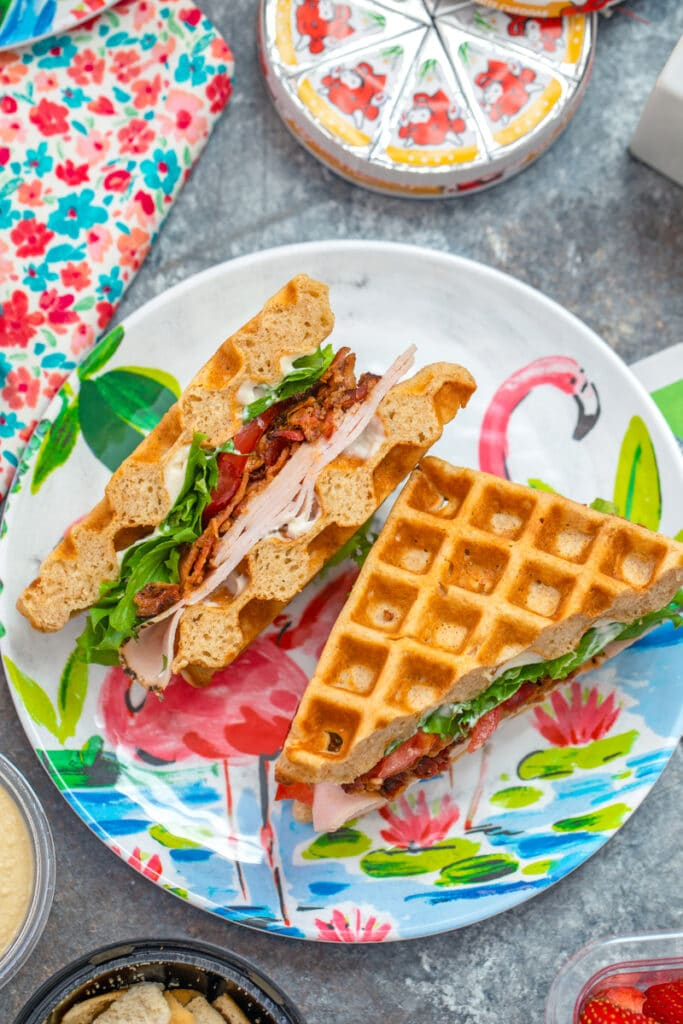 Overhead view of turkey BLT waffle sandwich on a fun flamingo plate with Laughing Cow cheese in background