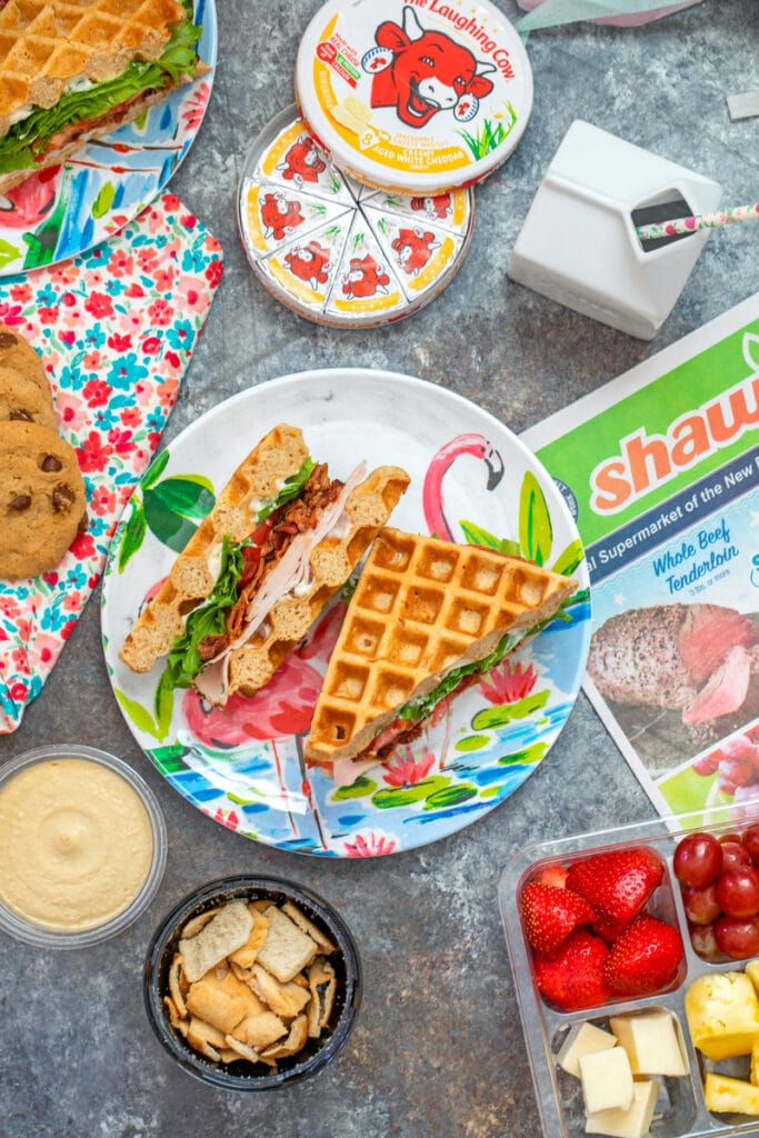 Overhead view of easy back-to-school lunch featuring turkey BLT waffle sandwich and all kinds of snacks