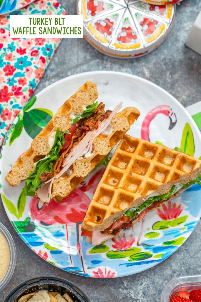 Overhead view of turkey BLT waffle sandwich on a fun flamingo plate with Laughing Cow cheese in background and recipe title at top