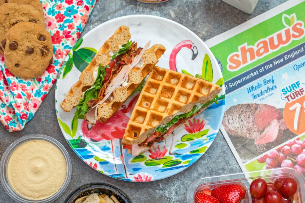 Overhead landscape view of a turkey BLT waffle sandwich surrounded by healthy back-to-school snacks