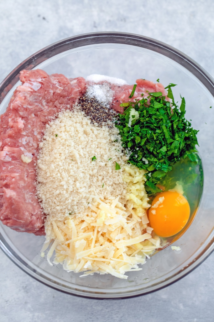 Overhead view of all of the ingredients for turkey meatballs in a bowl including ground turkey, panko, grated parmesan, egg, parsley, salt, and pepper