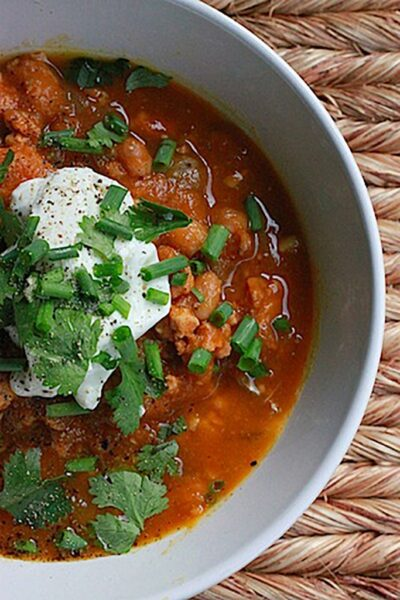 Overhead view of half a grey bowl filled with turkey white bean pumpkin chili, topped with sour cream, cilantro, and chives