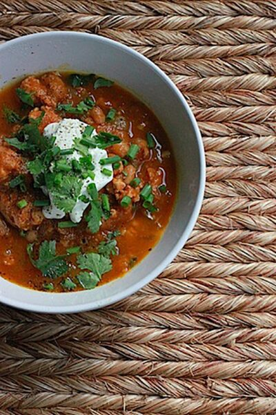 Overhead view of grey bowl of turkey white bean pumpkin chili topped with sour cream, cilantro, and chives on a burlap surface
