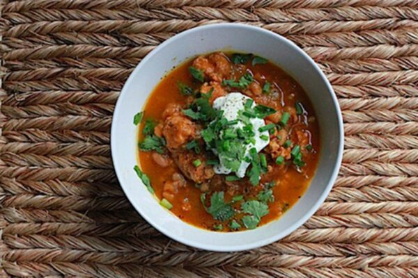 Landscape overhead photo of a grey bowl of turkey white bean pumpkin chili topped with sour cream, cilantro, and chives on a burlap surface
