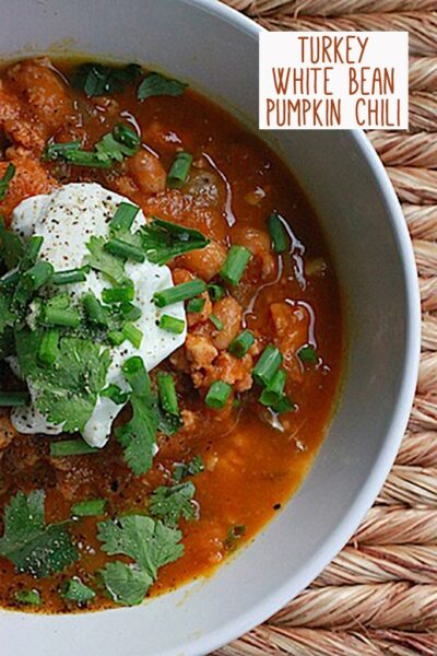 "Overhead view of half a grey bowl filled with turkey white bean pumpkin chili, topped with sour cream, cilantro, and chives with ""Turkey White Bean Pumpkin Chili"" text at top"