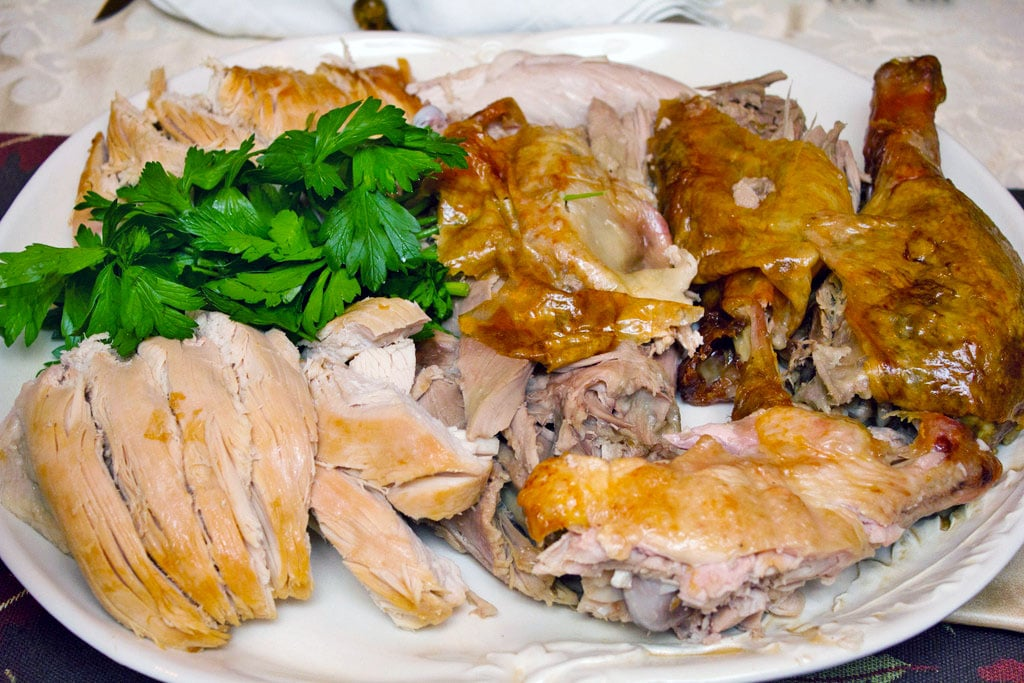 Platter with carved turkey on it, including sliced turkey breast, drumsticks, legs, and thighs with parsley garnish