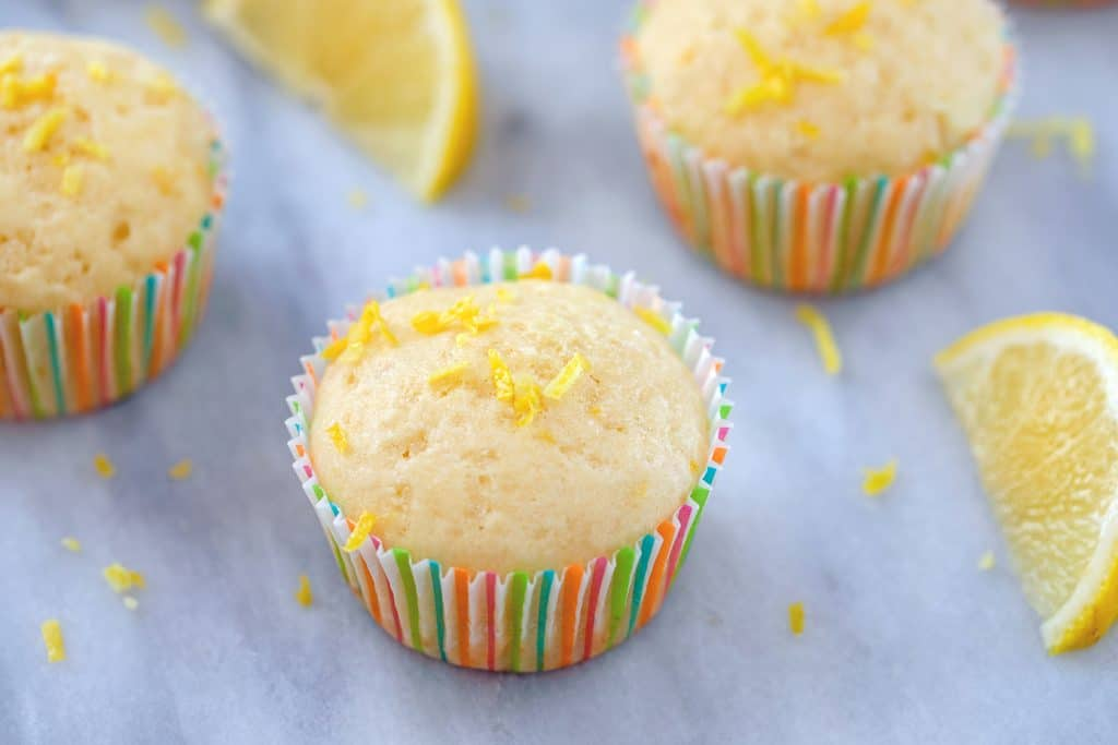 Landscape head-on photo of multiple Tuscan lemon muffins with lemon zest and lemon wedges scattered around