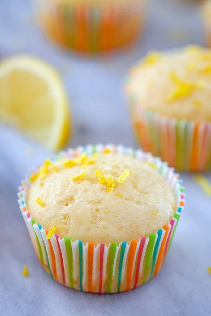 Head-on view of lemon muffin topped with lemon zest in a colorful muffin liner with a second muffin and lemon wedge in the background