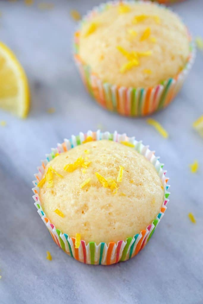 Two Tuscan lemon muffins on a marble surface with lemon zest scattered around and a lemon wedge in the background