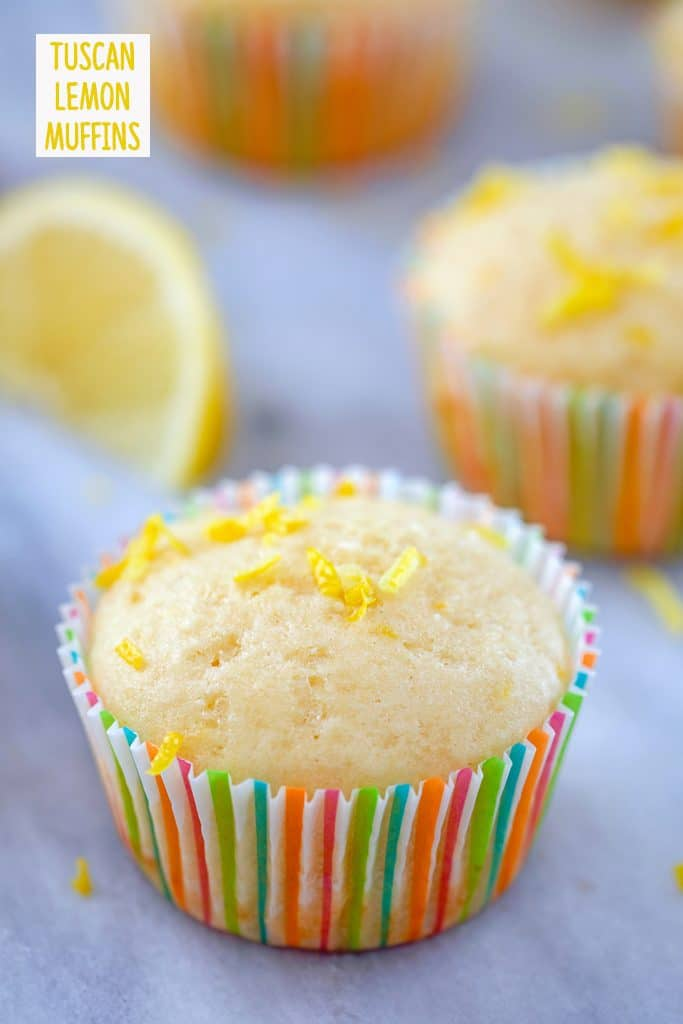 """Head-on view of lemon muffin topped with lemon zest in a colorful muffin liner with a second muffin and lemon wedge in the background and """"Tuscan Lemon Muffins"""" text at top"""