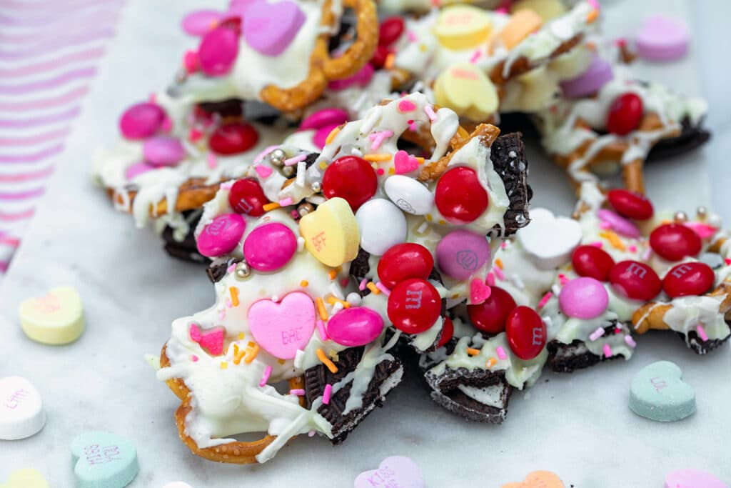 Landscape view of Valentine's Day bark with white chocolate and candy with conversation hearts sprinkled all around