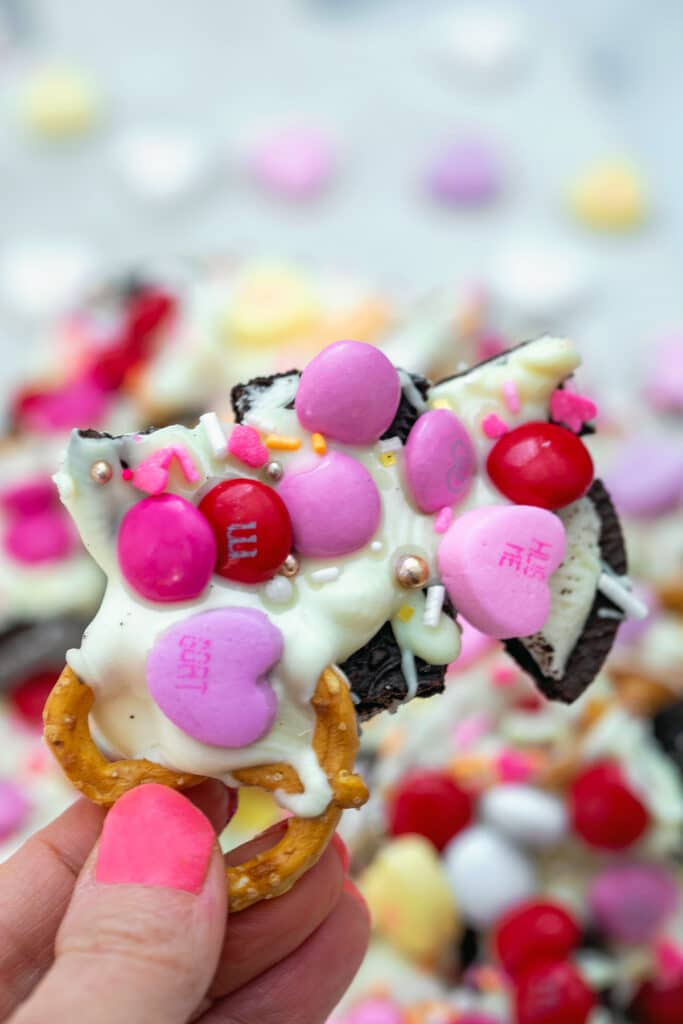 Hand holding up a piece of Valentine's Day bark with white chocolate and candy