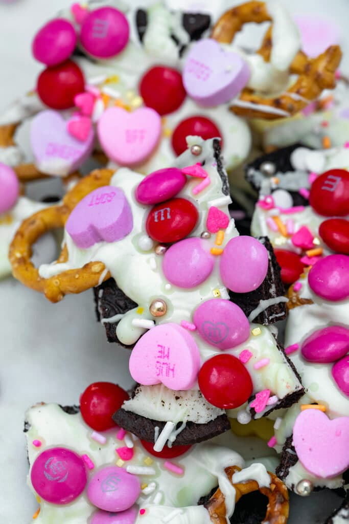Overhead view of pieces of Valentine's Day bark with white chocolate, M&Ms, conversation hearts, pretzels, and Oreo cookies