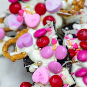 With Oreo cookies and pretzel twists covered in white chocolate and then topped with M&Ms, conversation hearts, and sprinkles, this Valentine's Day Bark will help you show your love this February 14!