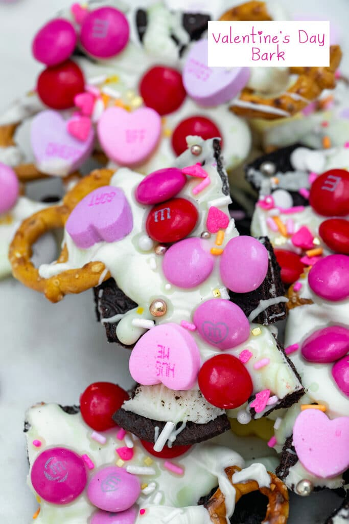 Overhead view of pieces of Valentine's Day bark with white chocolate, M&Ms, conversation hearts, pretzels, and Oreo with recipe title at top