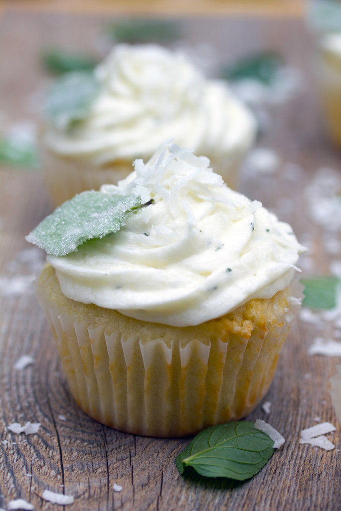 Head-on view of a coconut cupcake with white chocolate mint buttercream with shredded coconut and a sugared mint leaf on top