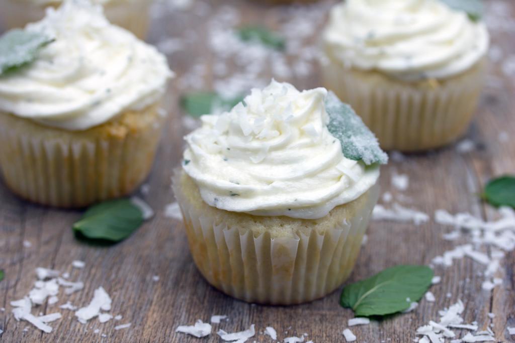 Landscape photo of a few coconut cupcakes with fresh mint chocolate buttercream surrounded by fresh chocolate mint leaves and shredded coconut